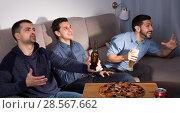 Купить «Happy men emotionally watching tv with beer and pizza at home», фото № 28567662, снято 10 января 2018 г. (c) Яков Филимонов / Фотобанк Лори