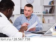 Купить «Concentrated businessman talking to colleague in office», фото № 28567738, снято 26 февраля 2018 г. (c) Яков Филимонов / Фотобанк Лори