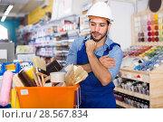 Купить «Workman standing folded arms near basket with picked tools in pa», фото № 28567834, снято 13 сентября 2017 г. (c) Яков Филимонов / Фотобанк Лори