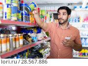 Man is choosing conserved peas using note list in supermarket. Стоковое фото, фотограф Яков Филимонов / Фотобанк Лори