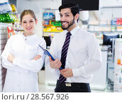 Купить «pharmacist and expert standing near shelves with medicines», фото № 28567926, снято 28 февраля 2018 г. (c) Яков Филимонов / Фотобанк Лори