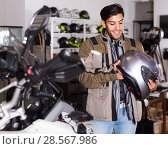 Купить «Man in moto jacket is choosing new helmet for motorbike in the store.», фото № 28567986, снято 1 сентября 2017 г. (c) Яков Филимонов / Фотобанк Лори
