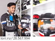 Купить «Man in moto jacket is choosing new helmet for motorbike in the store.», фото № 28567994, снято 1 сентября 2017 г. (c) Яков Филимонов / Фотобанк Лори