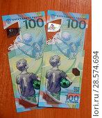 Купить «Новые банковские пластиковые банкноты достоинством 100 рублей, посвященные Чемпионату мира по футболу 2018 года», эксклюзивное фото № 28574694, снято 11 июня 2018 г. (c) lana1501 / Фотобанк Лори