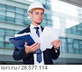 Купить «Smiling designer in suit and hat with folder is exploring documents with project», фото № 28577114, снято 3 июня 2017 г. (c) Яков Филимонов / Фотобанк Лори