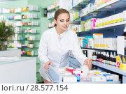 Купить «Woman pharmacist is looking different medicines in apothecary», фото № 28577154, снято 26 марта 2018 г. (c) Яков Филимонов / Фотобанк Лори