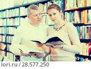 Купить «Intelligent couple choosing and discussing books», фото № 28577250, снято 22 февраля 2018 г. (c) Яков Филимонов / Фотобанк Лори