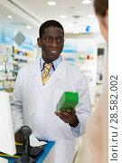 Купить «African American man pharmacist handing prescribed medicine to customer in pharmacy», фото № 28582002, снято 2 марта 2018 г. (c) Яков Филимонов / Фотобанк Лори