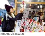 Купить «Woman choosing Christmas decoration at market», фото № 28582126, снято 22 декабря 2016 г. (c) Яков Филимонов / Фотобанк Лори
