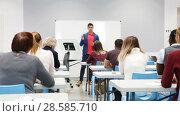 Купить «Smiling male teacher giving presentation for students in lecture hall», видеоролик № 28585710, снято 23 мая 2018 г. (c) Яков Филимонов / Фотобанк Лори