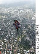 Купить «Парашютист в свободном полёте, прыгнувший с вертолёта Ми-8 над Петрозаводском, показывает рукой знак Окей», эксклюзивное фото № 28586178, снято 8 июня 2018 г. (c) Сергей Цепек / Фотобанк Лори