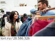 Купить «happy couple at vintage clothing store hanger», фото № 28586326, снято 30 ноября 2017 г. (c) Syda Productions / Фотобанк Лори