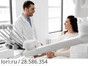 Купить «dentist talking to female patient at dental clinic», фото № 28586354, снято 22 апреля 2018 г. (c) Syda Productions / Фотобанк Лори
