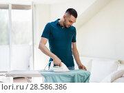 Купить «man ironing shirt by iron at home», фото № 28586386, снято 10 мая 2018 г. (c) Syda Productions / Фотобанк Лори