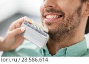 Купить «dentist choosing tooth color for patient at clinic», фото № 28586614, снято 22 апреля 2018 г. (c) Syda Productions / Фотобанк Лори