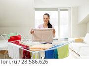 Купить «woman taking bath towels from drying rack at home», фото № 28586626, снято 29 апреля 2018 г. (c) Syda Productions / Фотобанк Лори