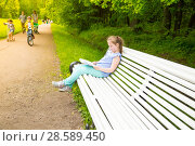 Купить «Girl sits on a bench in a park and reads a book», фото № 28589450, снято 11 июня 2017 г. (c) Сергей Дубров / Фотобанк Лори