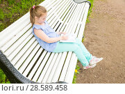 Купить «Schoolgirl sits on a bench and reads a book», фото № 28589458, снято 11 июня 2017 г. (c) Сергей Дубров / Фотобанк Лори