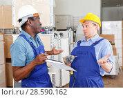 Купить «Construction workers discussing upcoming repairs», фото № 28590162, снято 4 мая 2018 г. (c) Яков Филимонов / Фотобанк Лори