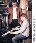 Купить «Father and teenage son examining keyboards in guitar shop», фото № 28590346, снято 29 марта 2017 г. (c) Яков Филимонов / Фотобанк Лори