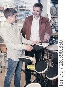 Купить «Father and teenage son examining drum units in guitar shop», фото № 28590350, снято 29 марта 2017 г. (c) Яков Филимонов / Фотобанк Лори