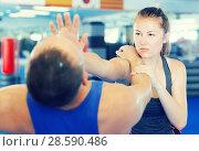 Купить «Woman and trainer practicing punches in gym», фото № 28590486, снято 21 августа 2017 г. (c) Яков Филимонов / Фотобанк Лори