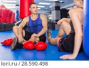 Купить «Female boxer is sitting with man and talking about healthy in gym.», фото № 28590498, снято 21 августа 2017 г. (c) Яков Филимонов / Фотобанк Лори