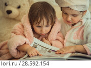 Купить «Little sisters in plush robe riding the book», фото № 28592154, снято 20 февраля 2017 г. (c) Julia Shepeleva / Фотобанк Лори