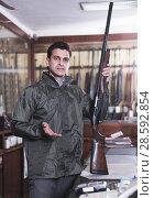 Купить «Man choosing rifle in shop», фото № 28592854, снято 11 декабря 2017 г. (c) Яков Филимонов / Фотобанк Лори