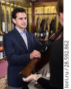 Купить «Man seller in gun shop showing rifle to woman client», фото № 28592862, снято 11 декабря 2017 г. (c) Яков Филимонов / Фотобанк Лори