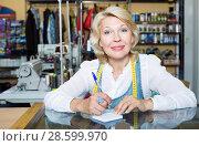 Купить «Tailor taking order at counter», фото № 28599970, снято 22 февраля 2019 г. (c) Яков Филимонов / Фотобанк Лори