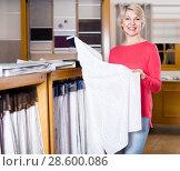 Купить «Ordinary woman choosing interesting fabric», фото № 28600086, снято 15 февраля 2017 г. (c) Яков Филимонов / Фотобанк Лори
