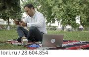 Купить «Young success businessman using tablet, laptop, mobile phone in the park», видеоролик № 28604854, снято 16 июля 2016 г. (c) Vasily Alexandrovich Gronskiy / Фотобанк Лори