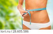 Купить «close up of woman body with measure tape on waist», фото № 28605586, снято 9 апреля 2017 г. (c) Syda Productions / Фотобанк Лори