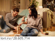 Купить «happy couple playing block-stacking game at home», фото № 28605714, снято 13 января 2018 г. (c) Syda Productions / Фотобанк Лори