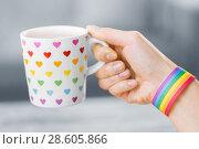 Купить «hand with cup of cacao and gay awareness wristband», фото № 28605866, снято 14 ноября 2017 г. (c) Syda Productions / Фотобанк Лори