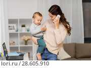 Купить «mother with baby calling on smartphone at home», фото № 28605910, снято 1 декабря 2017 г. (c) Syda Productions / Фотобанк Лори