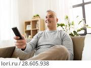 Купить «man with remote control watching tv at home», фото № 28605938, снято 14 апреля 2018 г. (c) Syda Productions / Фотобанк Лори