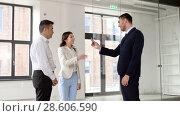 Купить «realtor giving key to customers at new office», видеоролик № 28606590, снято 12 июня 2018 г. (c) Syda Productions / Фотобанк Лори