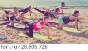 Купить «Sporty people practicing yoga on beach», фото № 28606726, снято 14 июня 2017 г. (c) Яков Филимонов / Фотобанк Лори