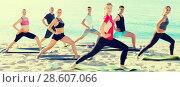 Купить «Sporty people practicing yoga on beach», фото № 28607066, снято 14 июня 2017 г. (c) Яков Филимонов / Фотобанк Лори