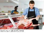 Купить «Skillful butcher processing carcase of young lamb for sale at butchery», фото № 28615918, снято 20 апреля 2018 г. (c) Яков Филимонов / Фотобанк Лори