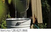 Купить «Man pouring down into a bucket freshly taken up water from a village draw-well at countryside», видеоролик № 28621866, снято 22 июня 2018 г. (c) Георгий Дзюра / Фотобанк Лори