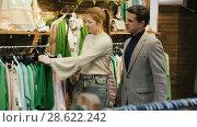 Купить «Couple is choosing jeans clothes for her in the clothes store.», видеоролик № 28622242, снято 27 марта 2018 г. (c) Яков Филимонов / Фотобанк Лори