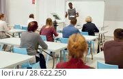 Купить «Smiling African American teacher giving presentation for students in lecture hall», видеоролик № 28622250, снято 23 мая 2018 г. (c) Яков Филимонов / Фотобанк Лори