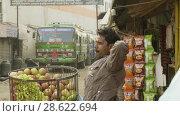 Купить «KATHMANDU, NEPAL - MARCH, 2018: Hindu man sells apples on the street, march, 2018», видеоролик № 28622694, снято 17 июня 2018 г. (c) Dzmitry Astapkovich / Фотобанк Лори
