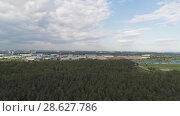 Купить «Flight over the forest. In the distance, on the horizon, you can see a large city», видеоролик № 28627786, снято 11 июня 2018 г. (c) Андрей Радченко / Фотобанк Лори