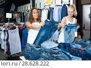 Купить «Two young girls choosing denim trousers», фото № 28628222, снято 17 августа 2018 г. (c) Яков Филимонов / Фотобанк Лори