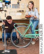 Купить «Couple is pumping the wheels on bicycle», фото № 28628390, снято 14 мая 2018 г. (c) Яков Филимонов / Фотобанк Лори