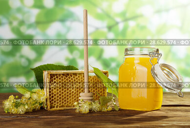 Bee products on table on light green background